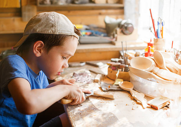 boy learning wood carving young carpenter working in a workshop carving craft activity stock pictures, royalty-free photos & images
