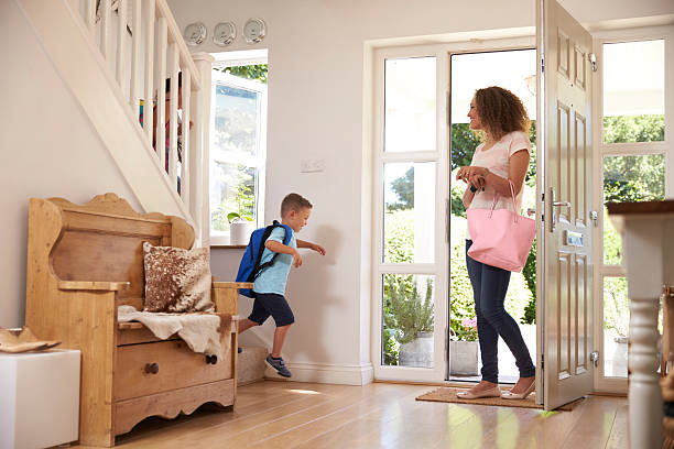 boy leaving home for school with mother - heimerziehung stock-fotos und bilder