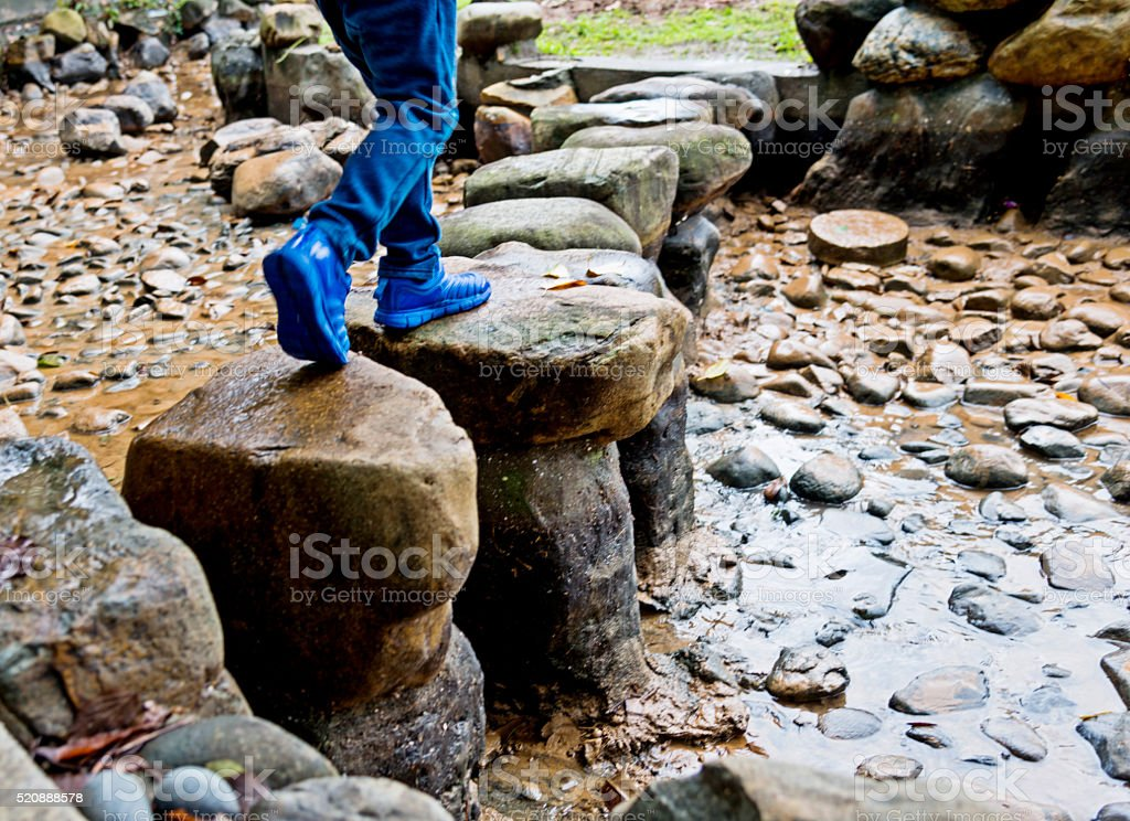 Boy legs crossing stepping stones stock photo