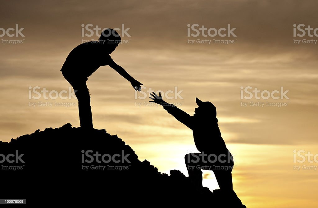 Boy Lending A Helping Hand to Friend Climbing stock photo