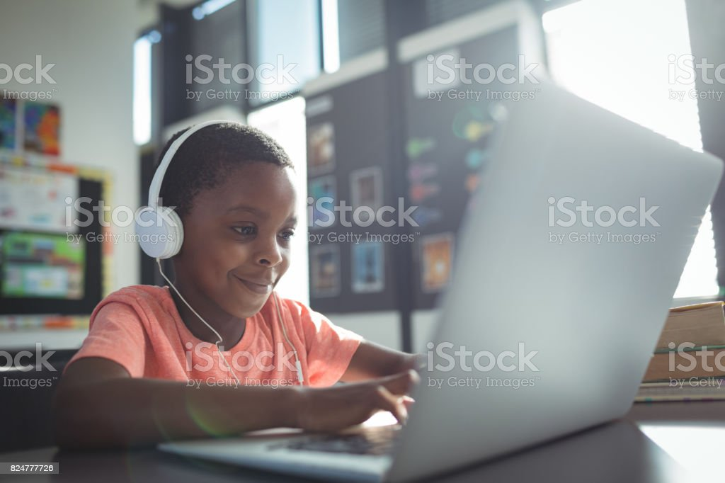 Boy listening music while using laptop stock photo