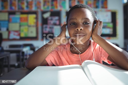 Portrait of boy listening music with headphones at desk in classroom