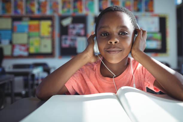 escuchar música de chico con los auriculares en el escritorio - auriculares equipo de música fotografías e imágenes de stock