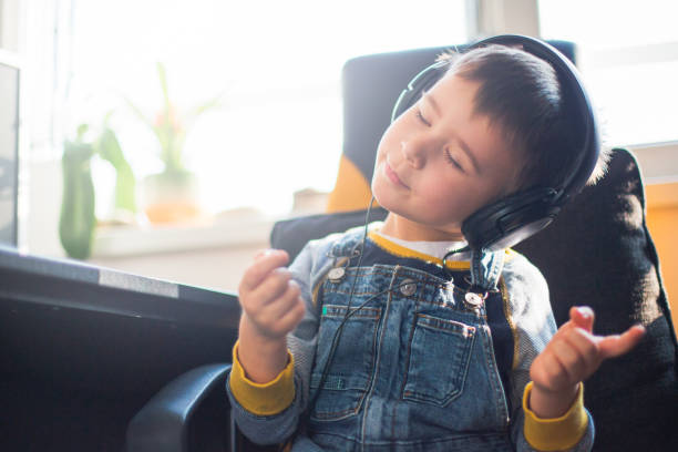 Boy listening to music wearing headphones Cute boy listening to music wearing headphones bib overalls boy stock pictures, royalty-free photos & images