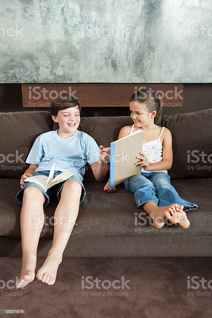 Boy looking at a picture his sister has drawn stock photo