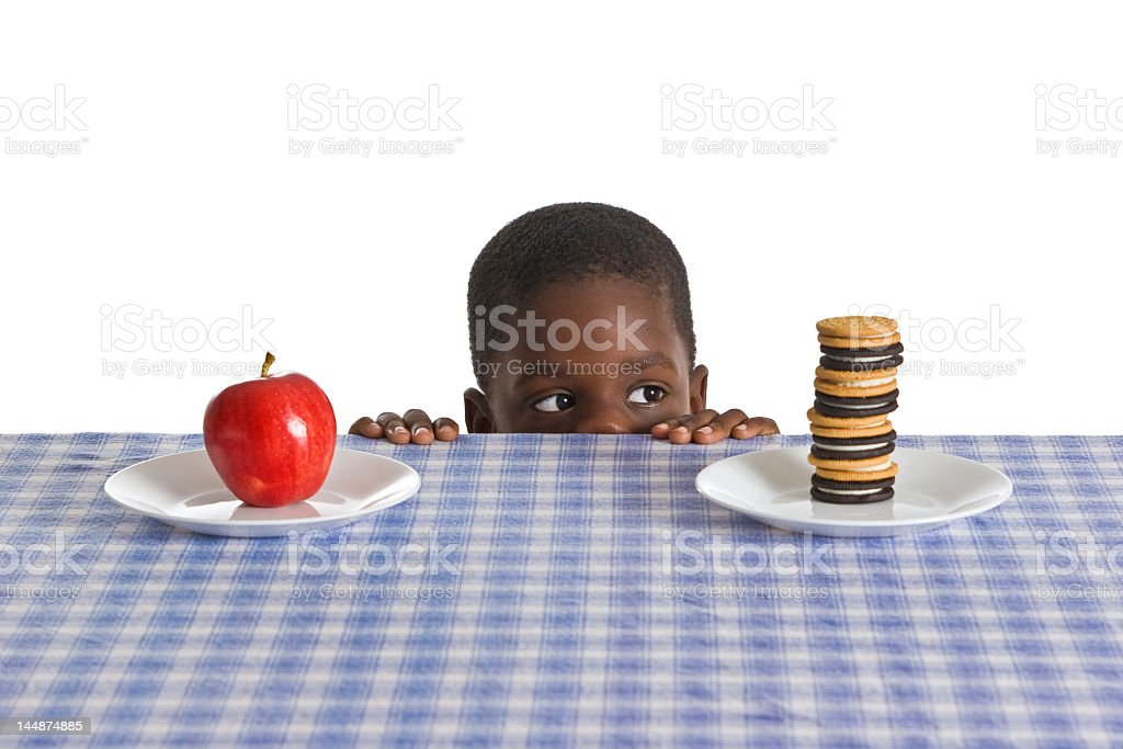 Boy looking at an apple on a plate and a stack of Oreos stock photo