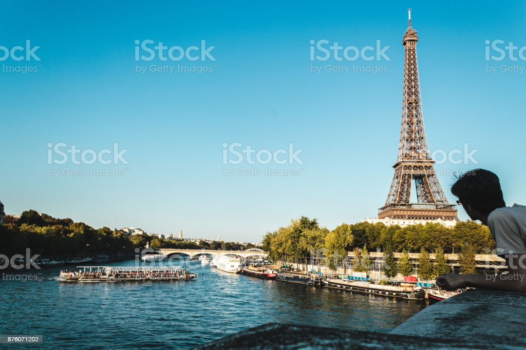 Boy Looking at Eiffel Tower and The Seine River in Paris, France stock photo