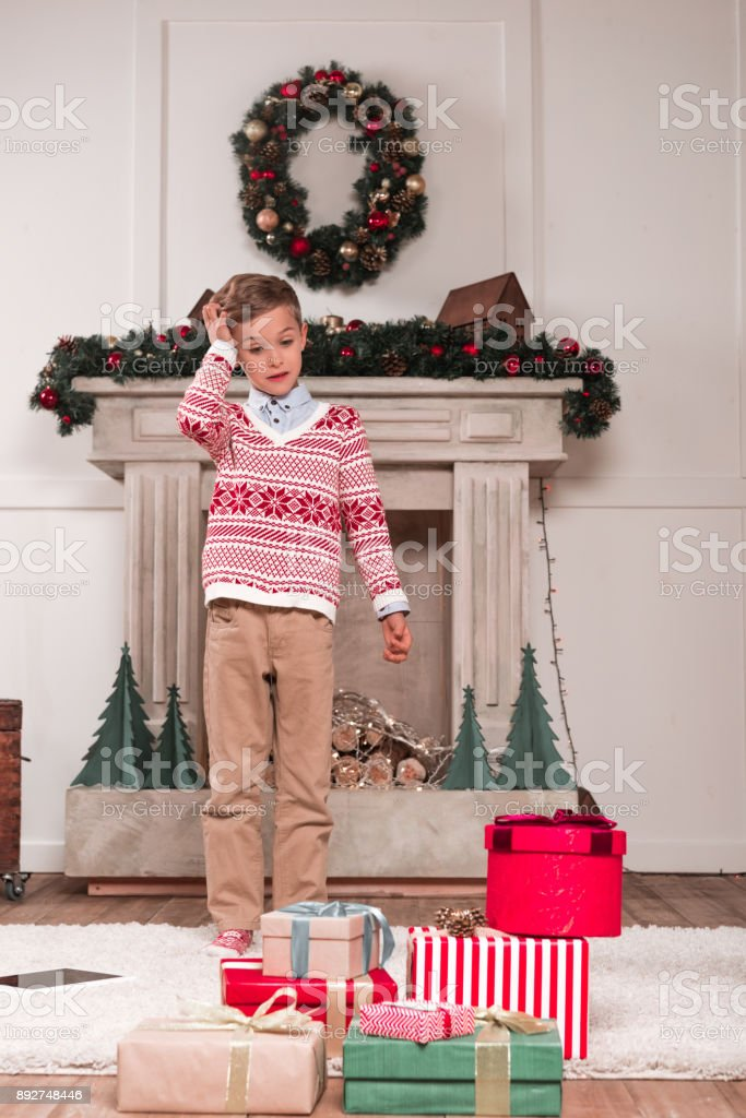 boy looking at heap of gifts stock photo