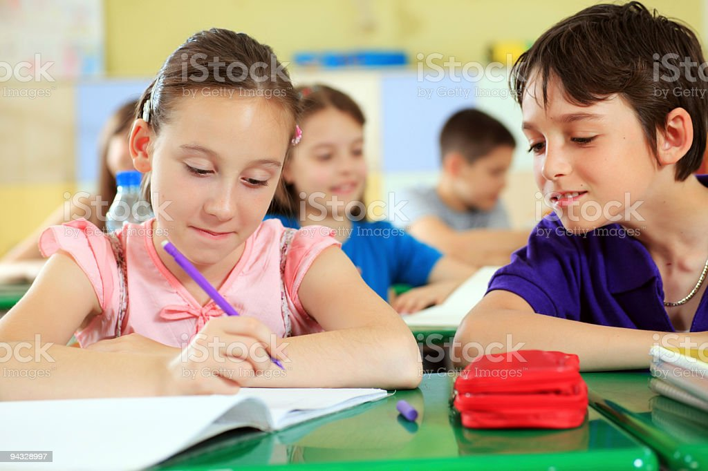 Boy looking at his classmate copybook. royalty-free stock photo
