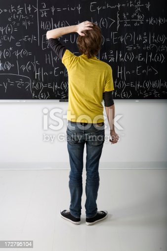 istock Boy looking at math problem on blackboard 172795104