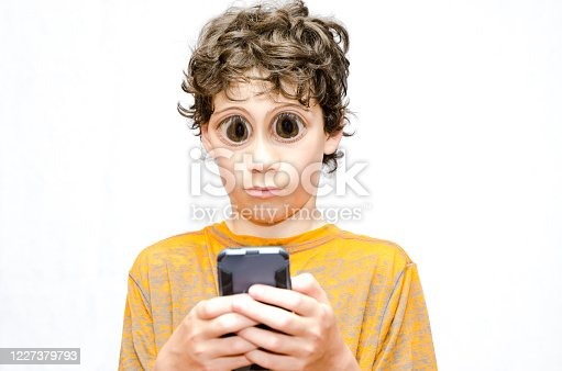 Boy looking at mobile phone with bulging eyes on a white background