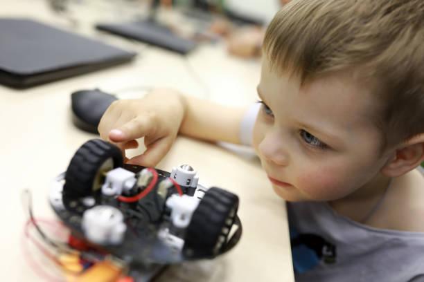junge blick auf roboter - kindergarten workshop stock-fotos und bilder