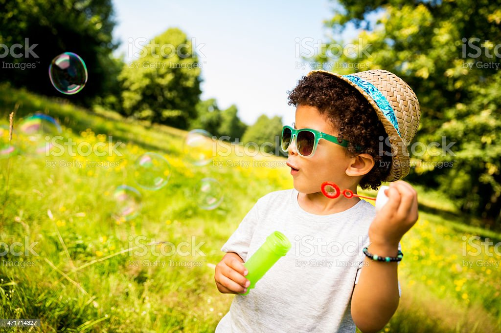 Boy looking at soap bubbles stock photo