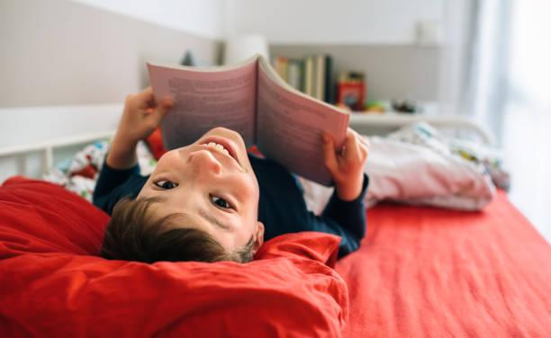 책을 읽는 동안 카메라를 찾는 소년 - 십대 소년 뉴스 사진 이미지