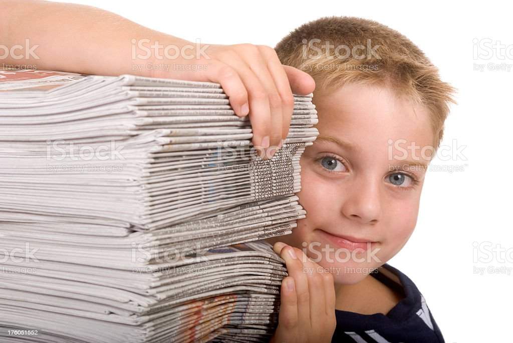 Boy looking from behind newspaper recycling, delivery stack, Isolated royalty-free stock photo