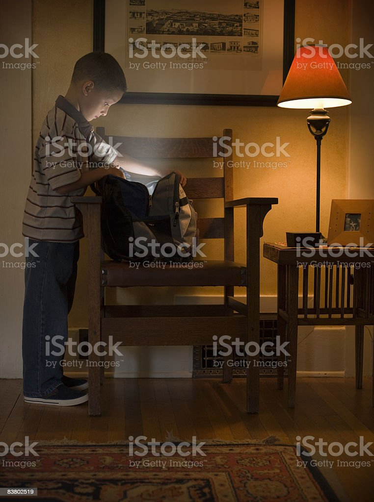 Petit garçon à la recherche d'un sac à dos léger, qui en sortent photo libre de droits