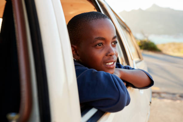boy looking out of car window on family road trip - boy looking out window stock pictures, royalty-free photos & images