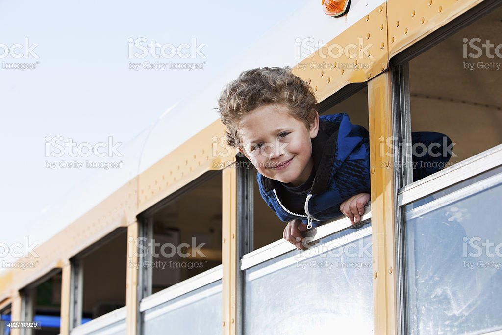 Boy looking out school bus window stock photo