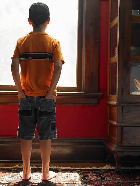 Boy (8-10) looking out window, hands in pockets, rear view stock photo