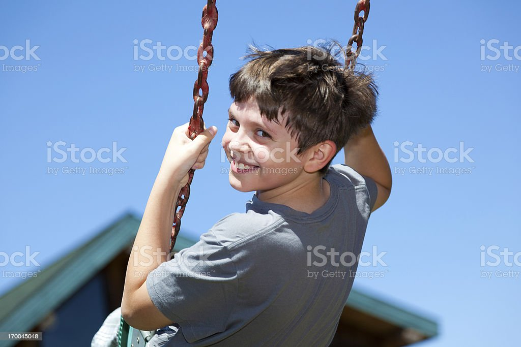 Boy looking over shoulder at camera smiling on swing. stock photo