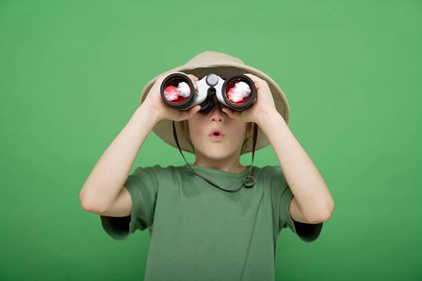 boy looking through binocular against green background stock photo