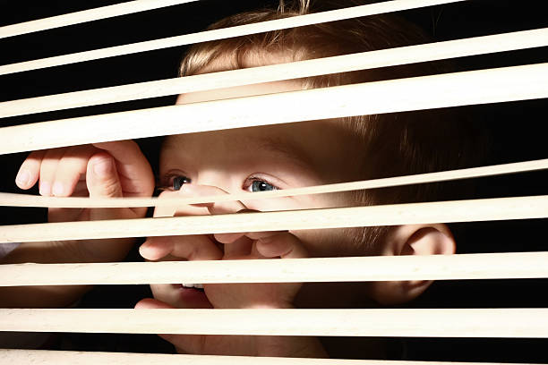 Boy looking through blinds stock photo
