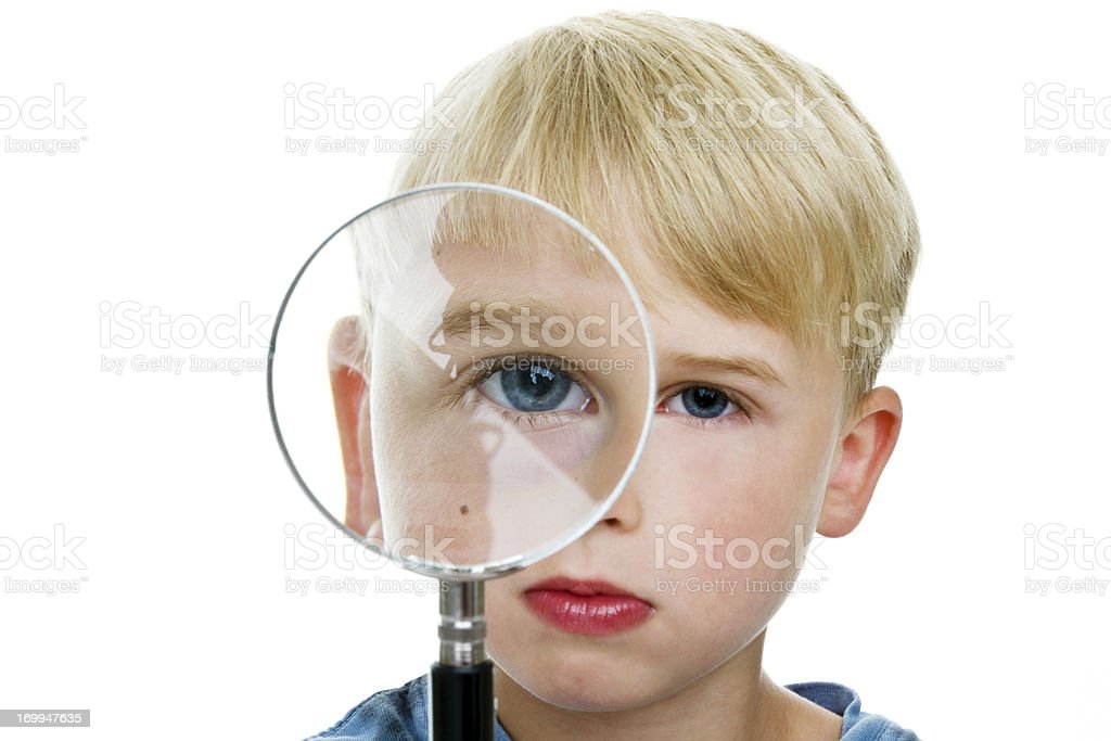 Boy looking through magnifying glass royalty-free stock photo