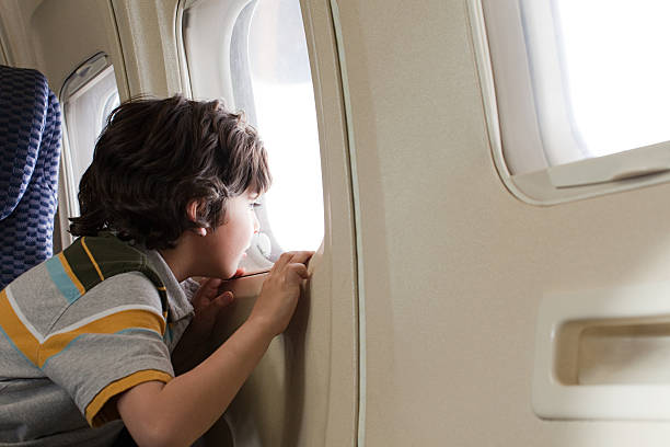boy looking through window on an airplane - boy looking out window stock pictures, royalty-free photos & images
