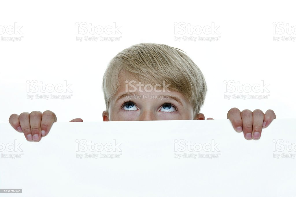Boy looking up from behind a wall royalty-free stock photo