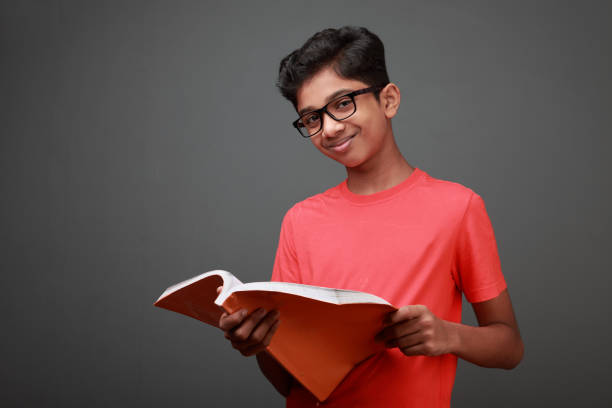Boy looks as he holds a book in hand stock photo