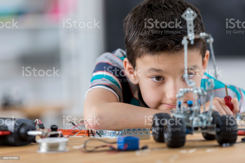 Boy looks at robot he created in technology class stock photo
