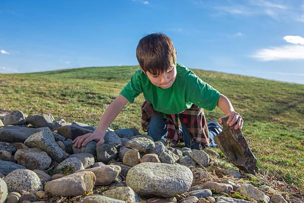 Boy looks under a rock. stock photo