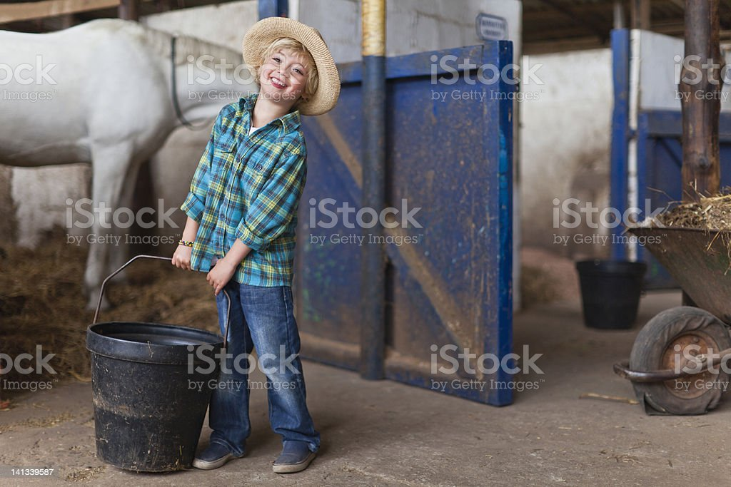 Boy lugging bucket in stable stock photo