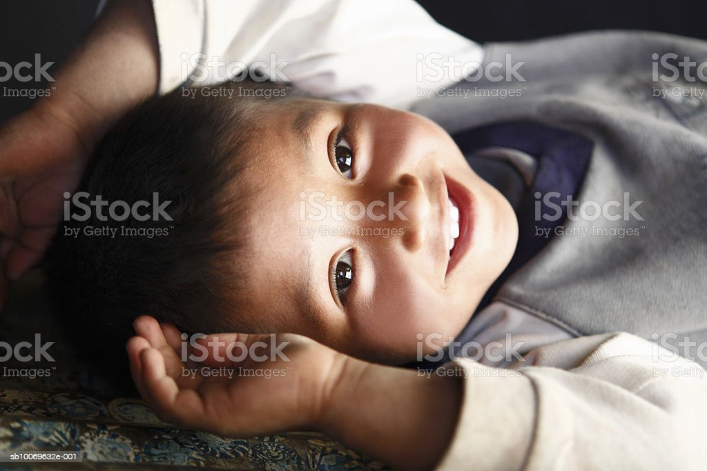 Boy (18-23 months) lying down and smiling, portrait, close-up royalty free stockfoto