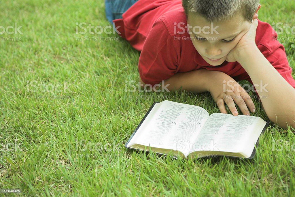 Boy lying grass reading a book stock photo