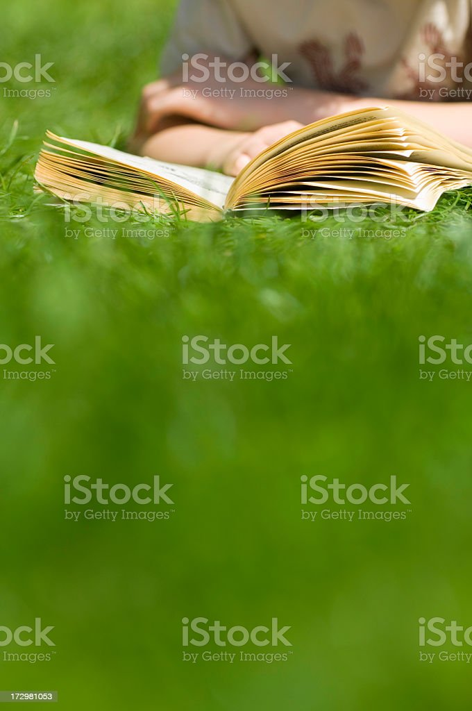 Boy lying in grass reading a book royalty-free stock photo