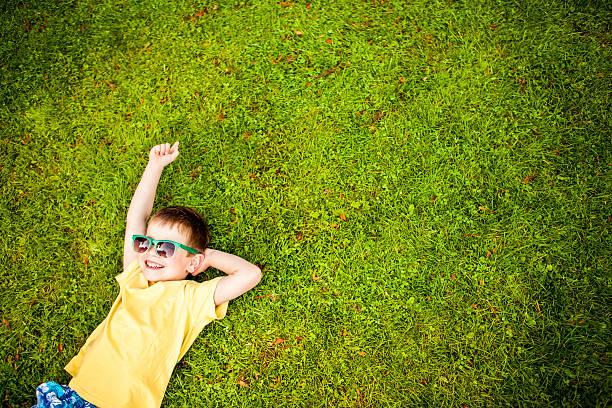 junge liegen auf gras - sonnenbrille kleinkind stock-fotos und bilder