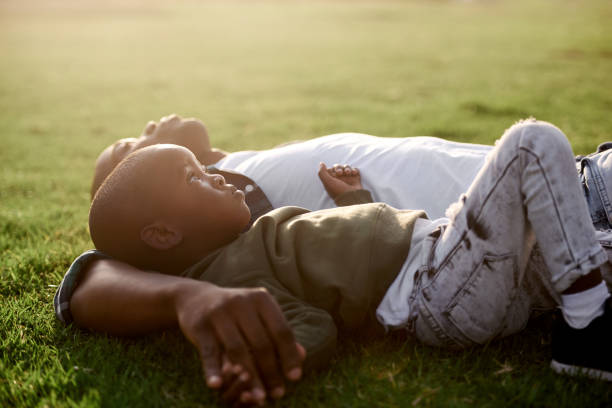 Boy lying on grass with dad close family stock photo