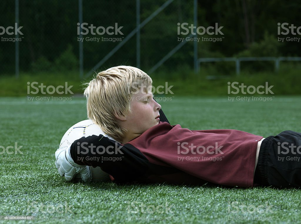 Boy (8-9 years) lying on grass with soccer ball under head, side view foto de stock libre de derechos