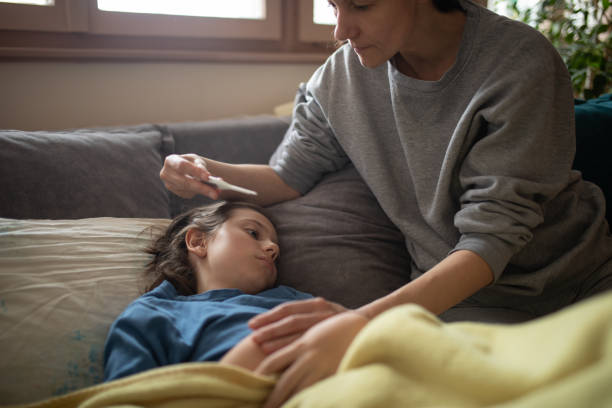 Boy lying sick on sofa and his mother taking care for him stock photo