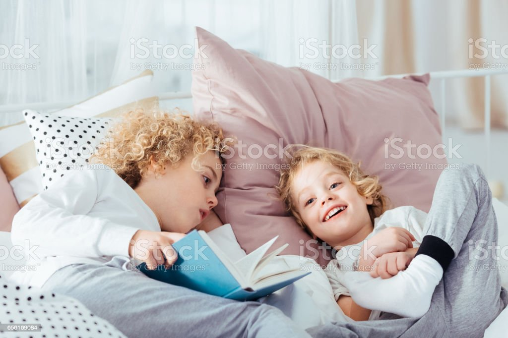 Boy lying with book stock photo