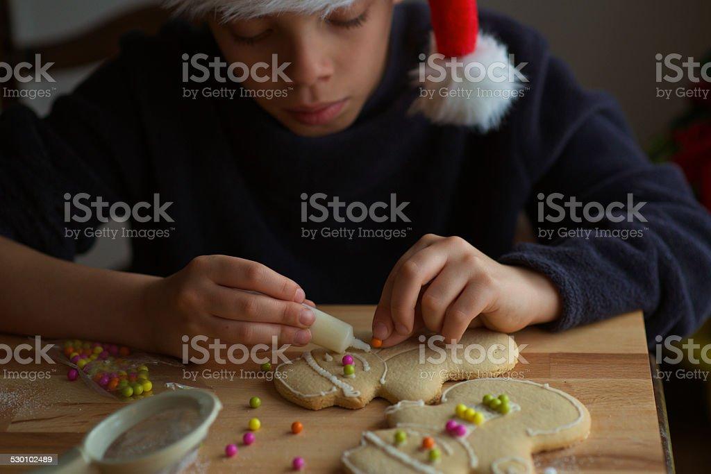 boy make christmas ginger bread man cookies stock photo