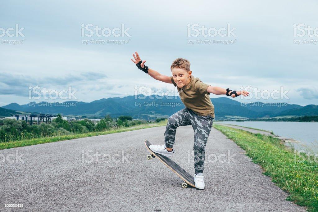 Boy makes a trick on skateboard stock photo