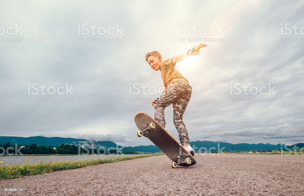 Boy makes a trick with skateboard stock photo