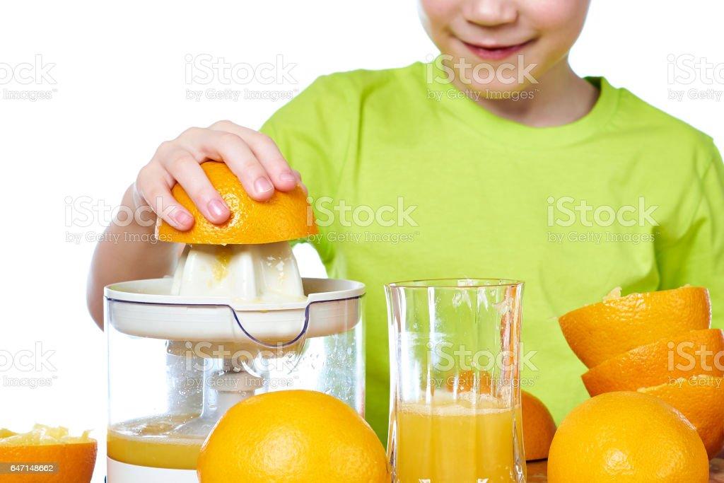 Boy makes orange juice isolated stock photo