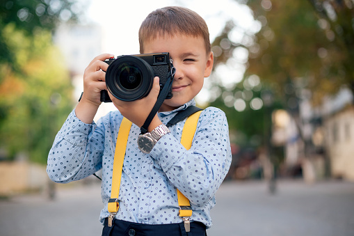 istock Boy makes pictures on film retro style digital camera 962175188