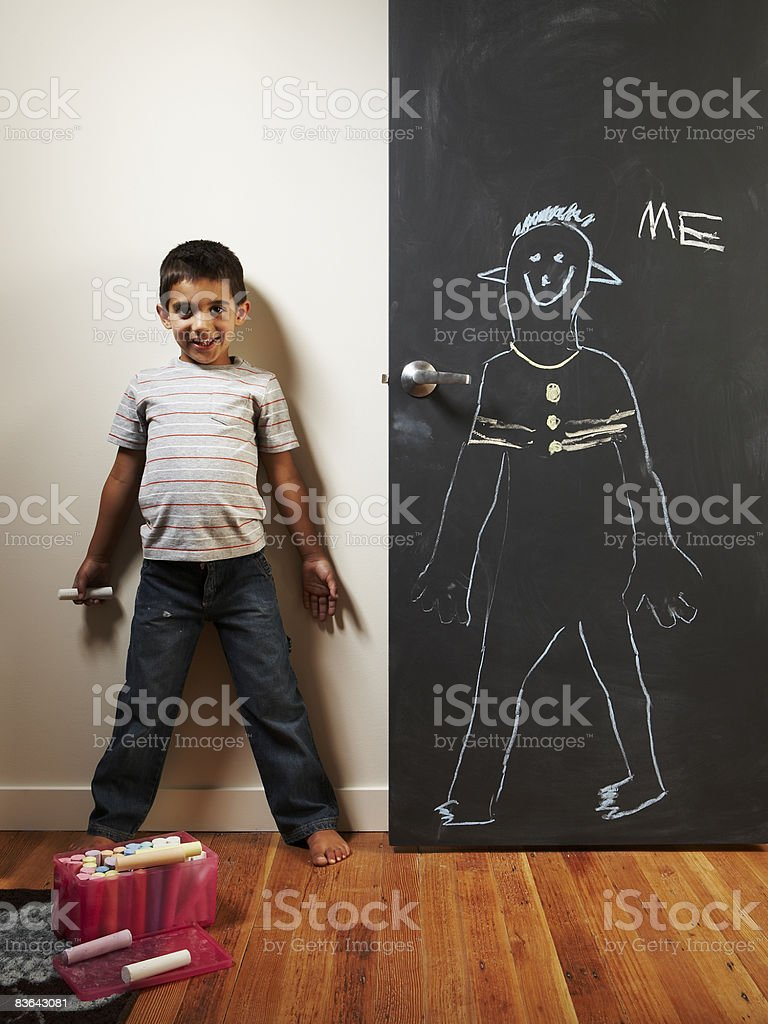 Niño haciendo un chaulk dibujo de él foto de stock libre de derechos