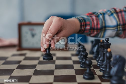 Two young boys, playing chess in school of chess.