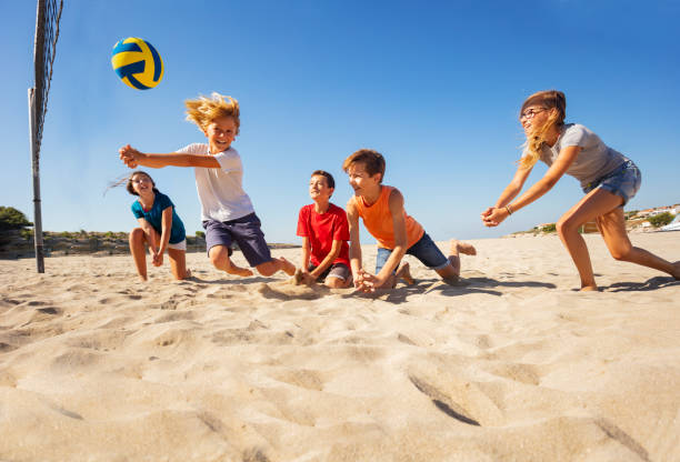 Boy making bump pass during beach volleyball game stock photo