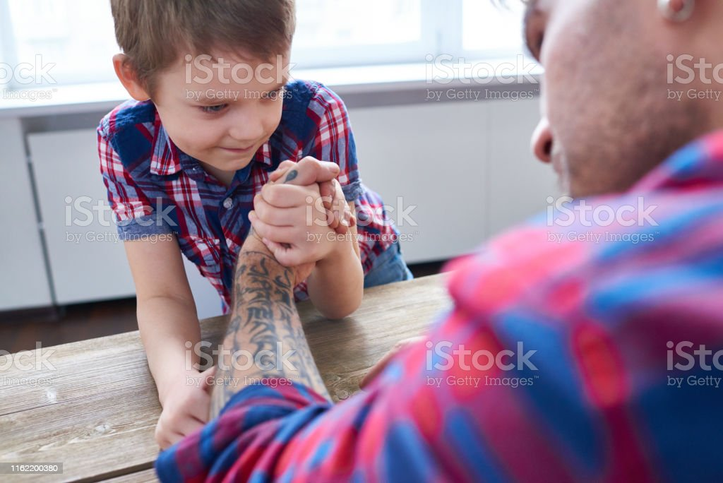 Happy little boy at wooden table arm wrestling with tattooed man